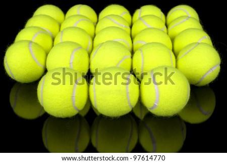 Symmetrical arrangement of tennis balls on black reflective surface. - stock photo