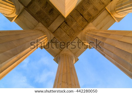 Symmetrical Ceiling at Top Corner of Lincoln Memorial Roof during early morning DC Sunrise. The Columns and marble are lit by the sun and cast shadows. The composition utilizes symmetry. - stock photo