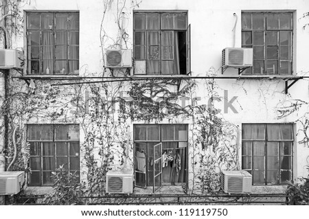 Symmetrical glass windows on a dilapidated concrete wall in monochrome, for concept of urban living. - stock photo