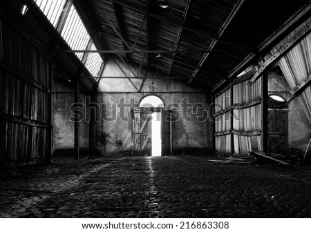Symmetrical image of an abandoned barn near the Antwerp harbor, with the door standing open exactly in the middle leading the light beams into the barn - stock photo