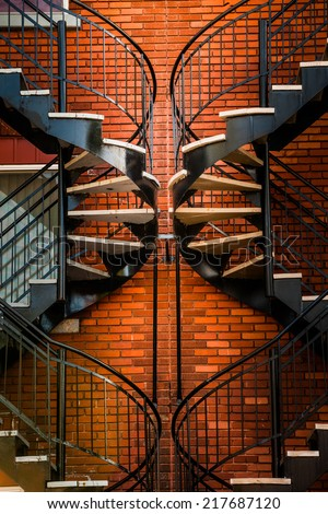 Symmetrical Spinning Staircases and beautiful Orange Brick Wall - stock photo