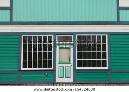 Symmetrical view of the front door and entrance to a quaint green wooden house with large cottage pane windows on either side - stock photo