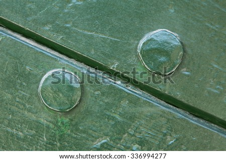 Symmetrical wood and nail texture background with two green painted planks of wood in a diagonal position with the head of one nail in each board, full frame.