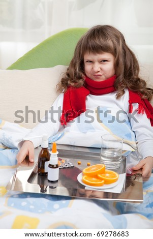 Sympathetic little sick girl with wry face in red scarf under blanket in bed is taking a salver with pills, sprays and orange - stock photo
