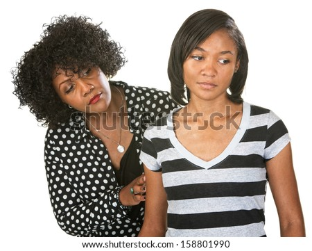 Sympathetic mother touching the arm of sad teenage daughter - stock photo
