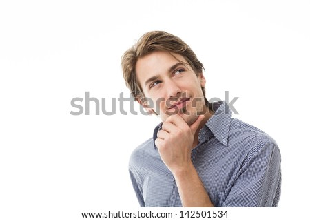 Sympathetic thoughtful man standing with his hand to his chin staring thoughtfully upwards isolated on white