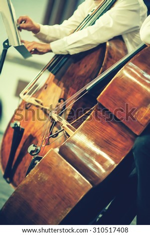 Symphony orchestra on stage, hands playing violin. Shallow depth of field, vintage style. - stock photo