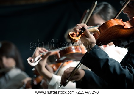 Symphony orchestra violinists performing on stage against dark background. - stock photo