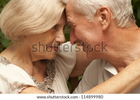 Sympothetic older couple sitting at a table at home on the veranda - stock photo