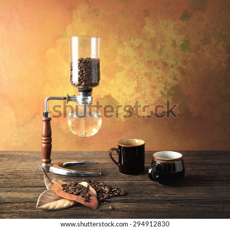 Syphon coffee preparing in the morning light and waiting two cups with bean and leaves - stock photo