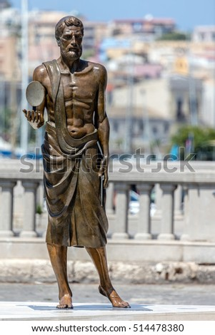 SYRACUSE, ITALY - AUGUST 14 2016: Bronze statue of Archimedes, holding a convex mirror in his right hand, sculpted by Pietro Syracuse Marchese, inaugurated in March 2016.