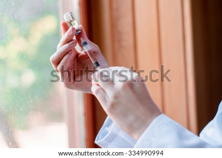 Syringe and ampule, bottle, medical injection in hand, palm or fingers. Medicine plastic vaccination equipment with needle. Nurse or doctor. Liquid drug or narcotic. Health care in hospital. - stock photo