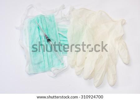 Syringe and needle on surgical mask and gloves. - stock photo