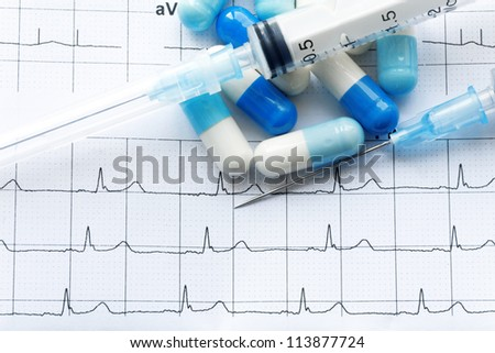 Syringe and tablets on the paper with graph of heart rhythm - stock photo