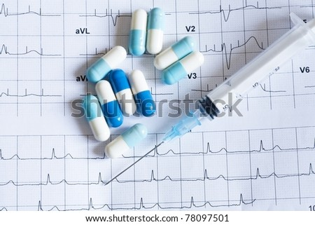 Syringe and tablets on the paper with graph of heart rhythm