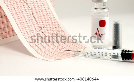 Syringe and vial on electrocardiograph. - stock photo