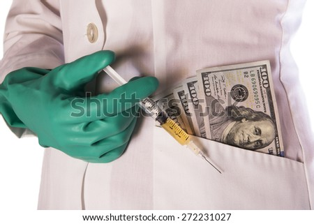 Syringe held by money in pocket of lab coat with green gloved hand