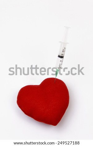 Syringe injecting a red heart on white background