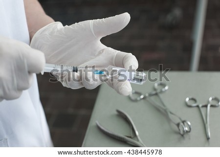 Syringe, medical injection, bottle, ampule in hand, palm or fingers. Medicine plastic vaccination equipment with needle. Nurse or doctor. Liquid drug or narcotic. Health care in hospital. - stock photo