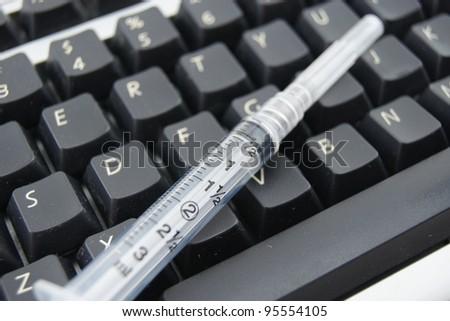 Syringe on keyboard - stock photo