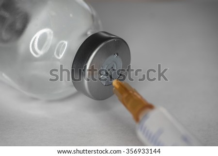 Syringe ready to put a vaccine from a vial, with focus on needle - stock photo