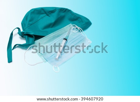 Syringe with doctor's hat and mask isolated on medical background - stock photo