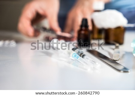 Syringe with glass vials and medications pills with defocused doctor's hands preparing for a treatment procedure - stock photo