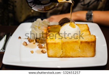 syrup being poured over a scoop of vanilla ice cream on toast