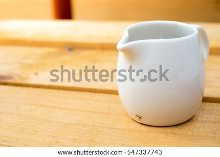 Syrup cup for coffee on the wooden table with small ant stick on it (sunlight)