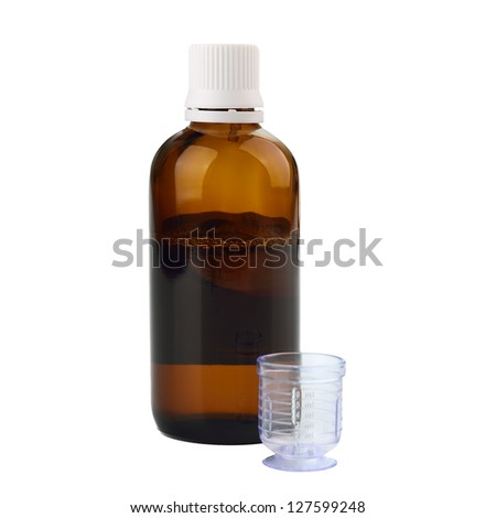 Syrup in a bottle with dosage cup for drinking