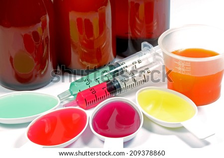 Syrup Medication Bottles, Medicine Cup, Medicine Spoons and Medicine Oral Syringe on White Background. - stock photo