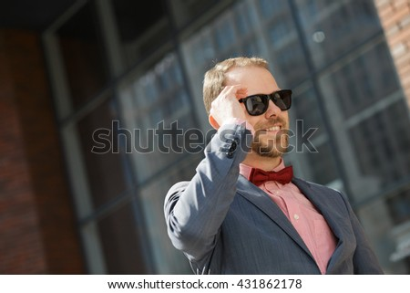 Sytlish businessman in sunglasses using smartphone at city downtown