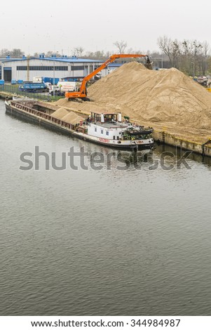 Szczecin, Poland - November 27, 2015: Excavator unloads sand from the ship on the river Regalica in Szczecin