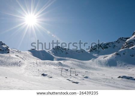 T-bar ski lift at high altitude alpine resort, direct sun with flare - stock photo