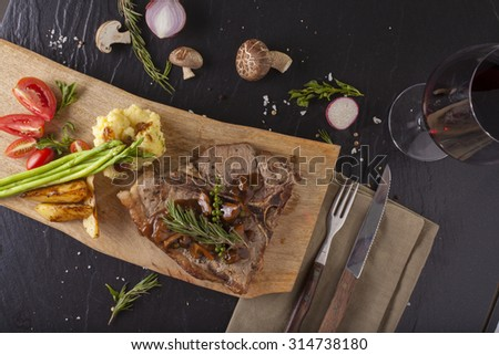 T-bone steak, a prepared piece of grilled T-bone steak brown sauce with mashed potato and vegetable on dining table with red wine decorated - stock photo
