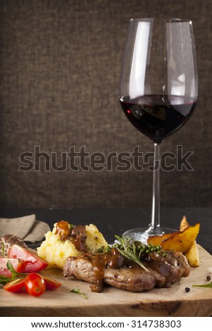 T-bone steak, a prepared piece of grilled T-bone steak brown sauce with mashed potato and vegetable on dining table with red wine decorated