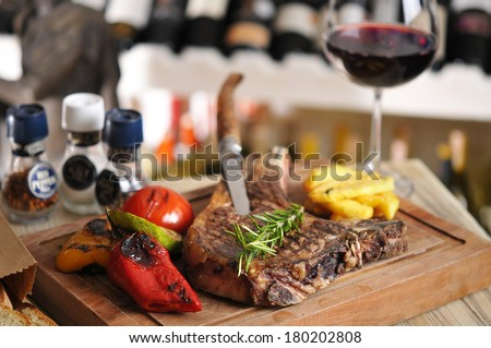 T-Bone steak barbecue with fried potato and red wine on wood table - stock photo
