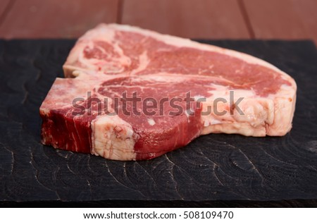 T-bone steak on a black cutting board