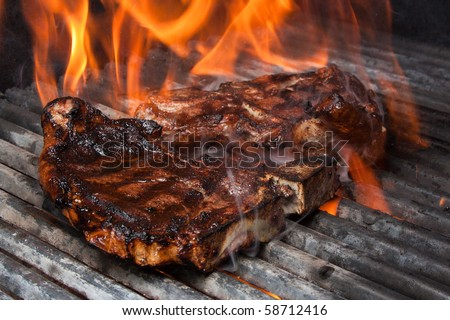 T-Bone Steak on Barbecue Grill Flames