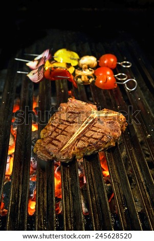T-bone steak on the barbecue grill with vegetable spears in the background - stock photo