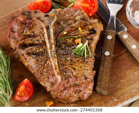 T-Bone Steak with Herbs on  a rustic wooden table - stock photo