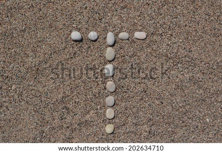 T letter made of stones on sand  - stock photo