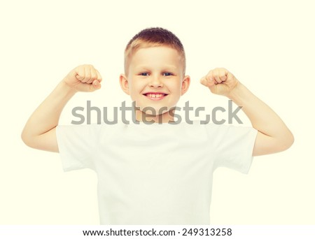 t-shirt design, strength, health, sport and fitness concept - little boy in blank white t-shirt showing muscles - stock photo