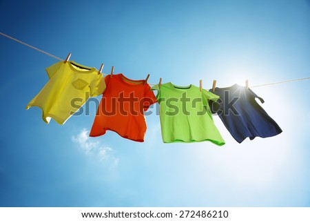 T-shirts hanging on a clothesline in front of blue sky and sun - stock photo