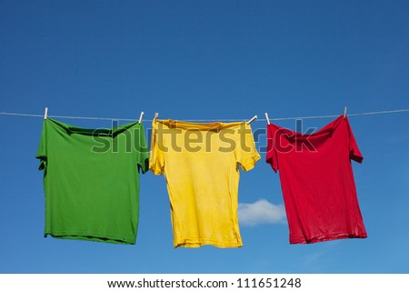 T-shirts on clothesline against blue sky.