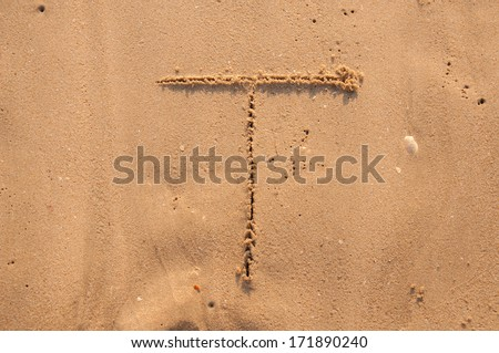 T text written in the sandy on the beach - stock photo