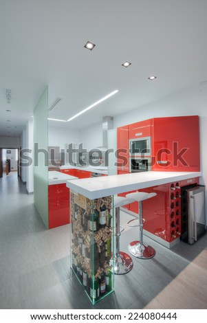 TA L'IBRAG, MALTA - SEPTEMBER 09, 2014: Modern gloss red kitchen and breakfast bar with a seamless top and with a wine bottles and corks feature leg in a modern apartment in Ta L'Ibrag, Malta.