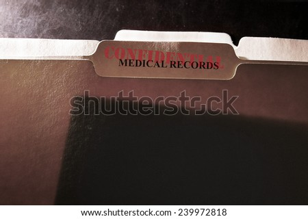 Tabbed file folders with Confidential and Medical Records text - stock photo