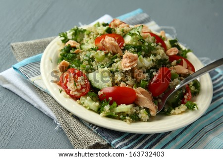 Tabbouleh salad with quinoa, salmon, tomatoes, cucumbers and parsley