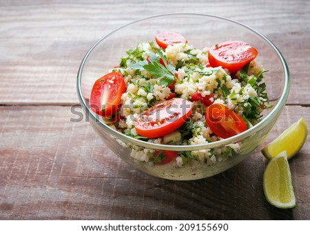 Tabbouleh with couscous and parsley, healthy salad in glass bowl on wooden table - stock photo